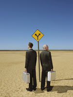 Two businessmen with briefcases standing by road sign in desert full length back view