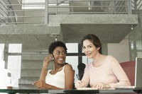 Two businesswomen in office one using mobile phone portrait