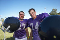 Two football players holding helmets on field portrait