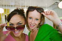 Popular : Two girls trying on sunglasses in boutique portrait close up