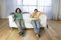 Two men sitting on sofa watching television