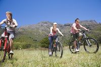 Popular : Two teenage boys and girl  16-17 years  biking mountains in background