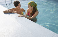 Popular : Two teenage girls  16-17  standing in swimming pool elevated view