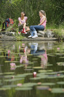 Popular : Two teenage girls  16-17 years  sitting on stones by lake smiling