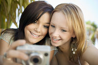 Two young women looking at pictures on digital camera in backyard front view
