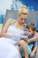 Woman and boy sitting on lounge chair reading a book together
