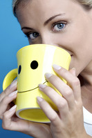Woman drinking from a cup with smiley face