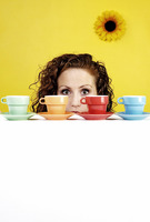 Woman hiding behind four colourful cups
