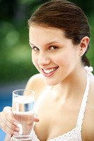 Woman holding a glass of water smiling