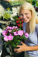 Woman holding flowers in plant nursery portrait