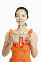 Woman holding shopping basket with sale label