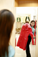 Woman holding up a coat while looking at the reflection in the mirror