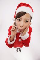 Woman in santa suit talking on the mobile phone