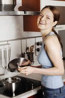 Woman laughing while cooking in the kitchen