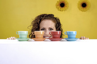 Woman looking at an arrangement of cups and saucers