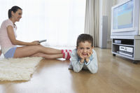 Woman sitting on floor watching television smiling boy  7-9  looking at camera