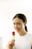 Woman smiling while holding a red rose