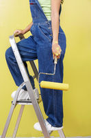 Woman standing on stepladder holding paint roller side view low section