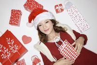 Woman surrounded by christmas gifts and shopping bags