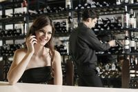Woman talking on the phone  man selecting wine bottle in the background