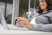Woman using laptop holding credit card sitting on porch