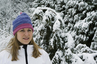 Woman wearing knit hat and winter clothing standing outdoor
