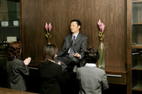 Women worshipping a businessman who is sitting on the shelf meditating