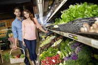 Young couple shopping for vegetables in supermarket