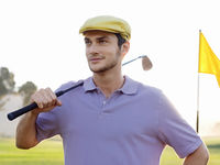 Popular : Young male golfer standing on course holding club on shoulder portrait