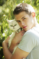 Young man holding a cat in his arms