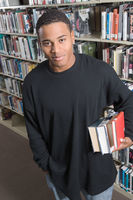 Young man holding books underarm in library
