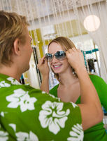 Young man putting sunglasses on girlfriend in clothing store