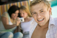 Young man sitting on patio smiling portrait