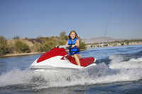 Young woman riding jetski on lake portrait