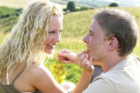 Lover : A blonde hair woman feeding her boyfriend grape