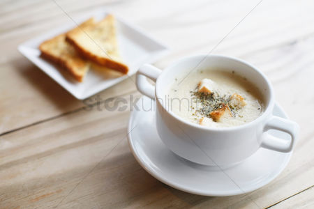 Two people : A bowl of soup with toast