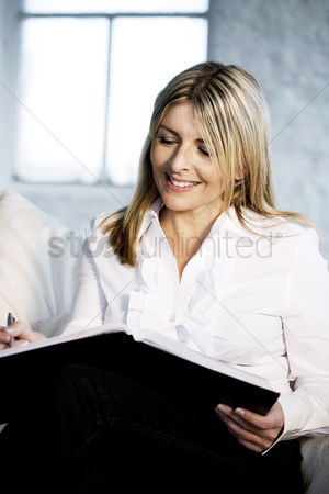 Tidy : A business lady showing satisfaction while writing