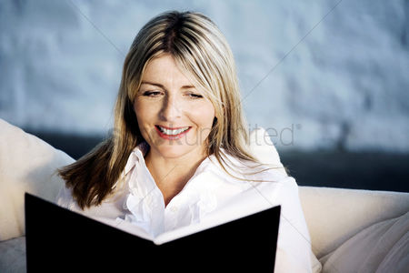 Adulthood : A business lady smiling while reading