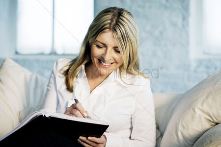 Cheerful : A business lady writing happily