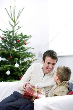 Adulthood : A father giving a christmas present to his son
