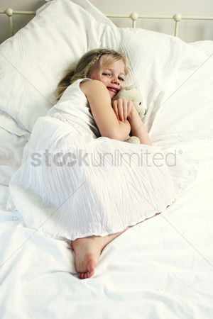 Adorable : A girl hugging a teddy bear on the bed
