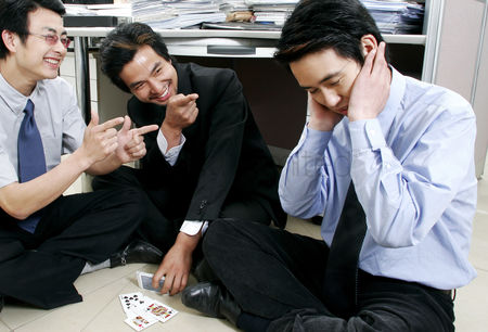 Having fun : A group of men playing cards in the office