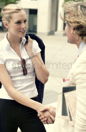 Client : A handshake between a woman in black pants and a man in white suit