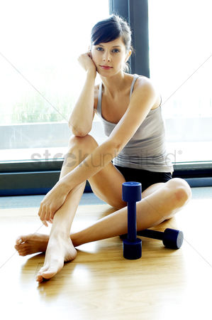 Dumbbell : A lady sitting on the floor with two dumbbells by her side