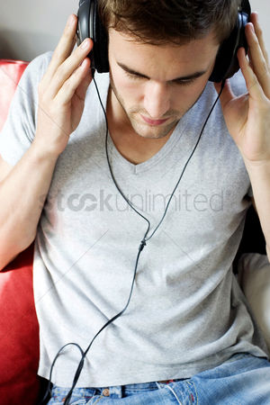 Adulthood : A man holding the headphone  listening to music
