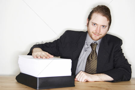 Determined : A man in business suit showing the stack of paperwork he has to finish