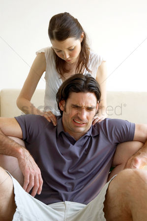 Pain : A man is in pain as his wife massaging his shoulder