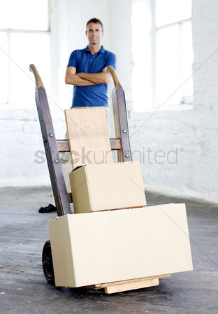 Strong : A man standing behind some goods that are ready to be delivered