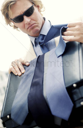 Choosing : A man with sunglass choosing a suitable tie to match his business suit