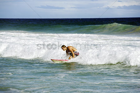 Excited : A muscular man surfing on the beach